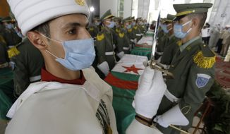 A soldier and members of the Algerian Republican Guard, guard the remains of 24 Algerians at the Moufdi-Zakaria culture palace in Algiers, Friday, July, 3, 2020. After decades in a French museum, the skulls of 24 Algerians decapitated for resisting French colonial forces were formally repatriated to Algeria in an elaborate ceremony led by the teary-eyed Algerian president. The return of the skulls was the result of years of efforts by Algerian historians, and comes amid a growing global reckoning with the legacy of colonialism. (AP Photo/Toufik Doudou)