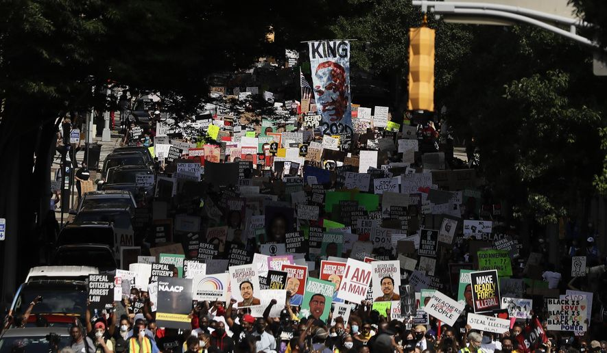"""In this June 15, 2020 file photo, people march down the street towards the Georgia state Capitol to protest against the mistreatment of black people and to press for policy change, in Atlanta. """"Lift Every Voice and Sing"""" was created more than a century ago. But the hymn dubbed as the Black national anthem has resurrected a beacon of hope during recent nationwide protests. (AP Photo/Brynn Anderson, File)"""