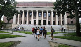In this Aug. 13, 2019, file photo, students walk near the Widener Library in Harvard Yard at Harvard University in Cambridge, Mass. The Ivy League school announced Monday, July 6, 2020, that as the coronavirus pandemic continues its freshman class will be invited to live on campus this fall, while most other undergraduates will be required learn remotely from home. (AP Photo/Charles Krupa, File)
