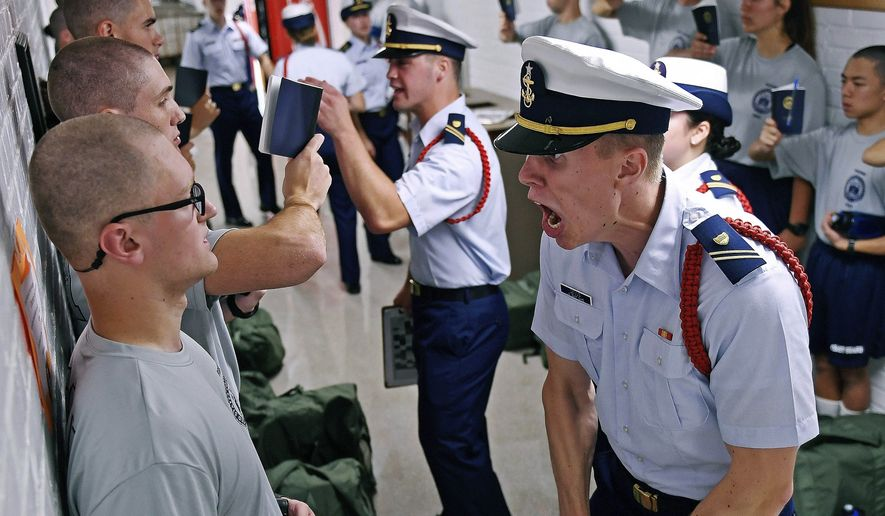 In this July 1, 2019, file photo, Whisky 2 company Cadre Jacob Denns, right, shouts instructions to swab Nicolas Fisher, left, of Pelham, N.H., on the first day of a seven-week indoctrination to military academy life for the Class of 2023 at the U.S. Coast Guard Academy in New London, Conn. The school, like other service academies and military training centers, has made major changes because of the coronavirus pandemic. (Sean D. Elliot/The Day via AP, File)
