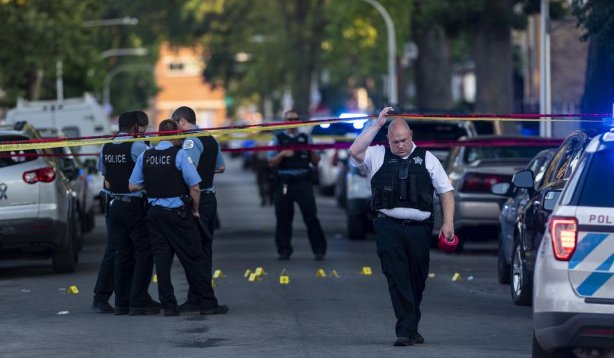 Chicago police officers investigate the scene of a deadly shooting in Chicago on Sunday, July 5, 2020, where a 7-year-old girl and a man were fatally shot during a Fourth of July party Saturday. At least a dozen people were killed in Chicago over the Fourth of July weekend, police said. Scores of people were shot and wounded. (Tyler LaRiviere/Chicago Sun-Times via AP)