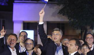 FILE - In this Sunday, July 5, 2020 file photo, Andrej Plenkovic, Croatia's Prime Minister incumbent, center, waves the Croatian flag as he celebrates with his party members in Zagreb, Croatia. According to partial results, the ruling conservatives overwhelmingly won the elections held Sunday. With over 90 percent of the vote counted, the Croatian Democratic Union (HDZ) has 66 seats in Croatia's 151-seat parliament and is likely to form a new coalition government with smaller right-wing groups. (AP Photo, File)
