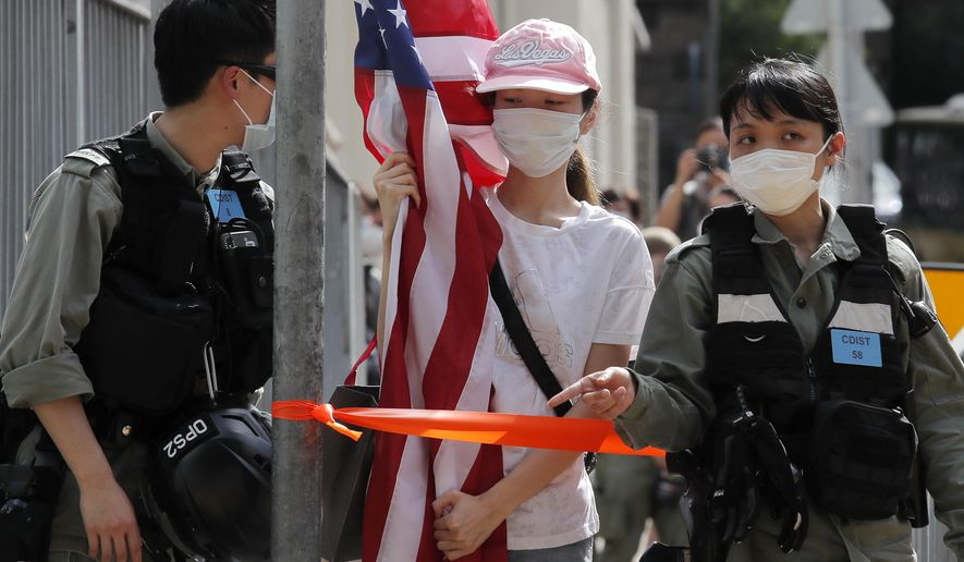"""A protester carrying an American flag as she is stopped by riot police during a protest outside the U.S. Consulate in Hong Kong, Saturday, July 4, 2020 to mark the American Independence Day or """"the Fourth of July."""" China's government and pro-Beijing activists in Hong Kong are condemning what they call foreign meddling in the territory's affairs, as countries move to offer Hong Kongers refuge and impose sanctions on China over a new security law. (AP Photo/Kin Cheung)"""