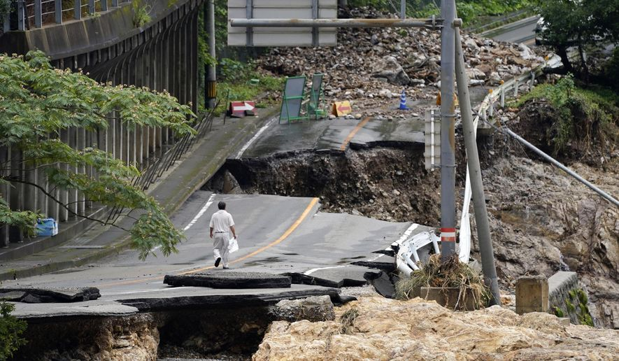 A man walks on heavily damaged road following a heavy rain in Kumamura, Kumamoto prefecture, southern Japan Monday, July 6, 2020. Rescue operations continued and rain threatened wider areas of the main island of Kyushu. (Koji Harada/Kyodo News via AP)