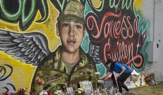 Mellisa Mendoza places white roses at a mural for Army Spc. Vanessa Guillen in Austin, Texas, on Monday July 6, 2020. Guillen went missing from Fort Hood in April, and is believed to have been killed by another soldier. The mural was created Saturday and Sunday by artists Fili Mendieta and Arturo Silva. (Jay Janner/Austin American-Statesman via AP)