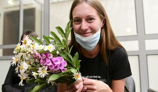 Russian journalist Svetlana Prokopyeva holds a bunch of flowers after a court session in Pskov, Russia, Monday, July 6, 2020. A court in the city of Pskov convicted Prokopyeva on charges of condoning terrorism on Monday and ordered her to pay a fine in a case that has been widely criticized as an attack on freedom of speech. (AP Photo)