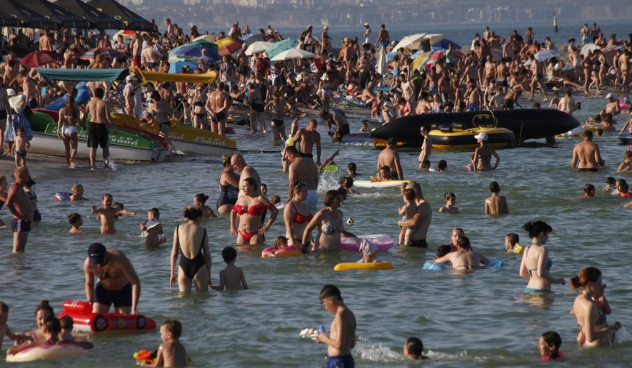People enjoy the beach in the Black Sea in Odessa, Ukraine, Saturday, July 4, 2020. Tens of thousands of vacation-goers in Russia and Ukraine have descended on Black Sea beaches, paying little attention to safety measures despite levels of contagion still remaining high in both countries. (AP Photo/Sergei Poliakov)