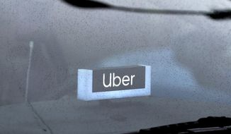FILE - In this May 15, 2020 file photo, an Uber sign is displayed inside a car in Chicago. Uber finally got its food delivery company, acquiring Postmates in a $2.65 billion all-stock deal, the ride-hailing giant confirmed Monday, July 6.  (AP Photo/Nam Y. Huh, File)