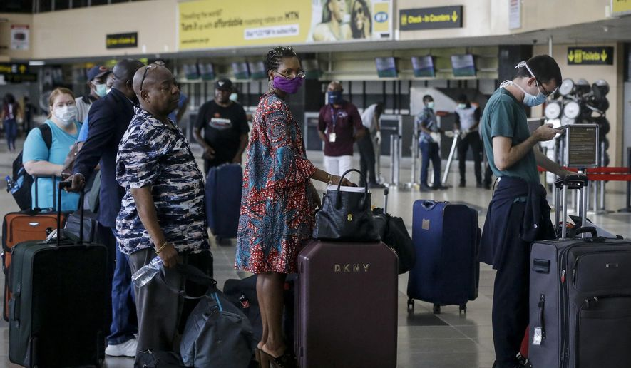 In this Tuesday, April 7, 2020, file photo, U.S. citizens queue to check in and be repatriated aboard an evacuation flight arranged by the U.S. embassy and chartered with Delta Air Lines, at the Murtala Mohammed International Airport in Lagos, Nigeria. African nations face a difficult choice as infections are rapidly rising: Welcome the international flights that originally brought COVID-19 to the ill-prepared continent, or further hurt their economies. (AP Photo/Sunday Alamba, File)