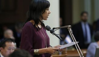 FILE - In this July 11, 2019, file photo, Assemblywoman Autumn Burke, D-Inglewood, calls on lawmakers to approve a wildfire measure she co-authored, with Assemblyman Chris Holden, D-Pasadena, and Assemblyman Chad Mayes, R-Yucca Valley, before the Assembly in Sacramento, Calif. A coronavirus outbreak in the California Legislature has indefinitely delayed the state Assembly's return to work from a scheduled summer recess. Assembly Speaker Anthony Rendon's office confirmed five people who work in the Assembly have tested positive for the coronavirus. They include Burke, who is believed to have contracted the virus while on the Assembly floor last month. (AP Photo/Rich Pedroncelli, File)