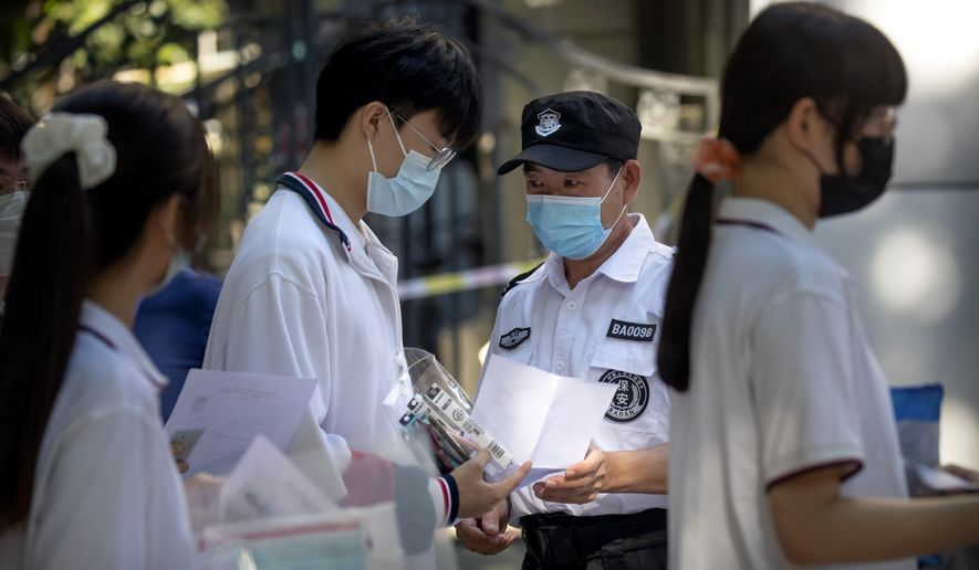 Students wearing face masks to protect against the new coronavirus have their documents checked by security officers before the first day of China's national college entrance examinations, known as the gaokao, in Beijing, Tuesday, July 7, 2020. China's college entrance exams began in Beijing on Tuesday after being delayed by a month due to the coronavirus outbreak. (AP Photo/Mark Schiefelbein)