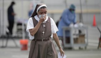 A nun with the Saint Ann Mission, who declined to give her name, leaves a COVID-19 testing site after being tested at the Martin Luther King, Jr. Clinica Campesina Health Center, during the coronavirus pandemic, Monday, July 6, 2020, in Homestead, Fla. The testing is sponsored by Community Health of South Florida. (AP Photo/Lynne Sladky)