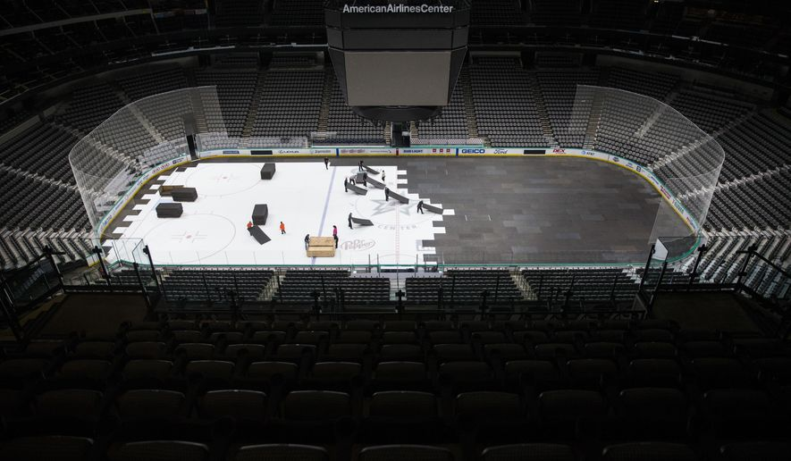 In this March 12, 2020, file photo, crews cover the ice at American Airlines Center in Dallas, home of the Dallas Stars hockey team, after the NHL season was put on hold due to the coronavirus.Deputy Commissioner Bill Daly told The Associated Press on Sunday, July 5, that the NHL and NHL Players' Association have agreed on protocols to resume the season. Daly said the sides are still negotiating a collective bargaining agreement extension. A CBA extension is still crucial to the process. (Ashley Landis/The Dallas Morning News via AP, File)  **FILE**