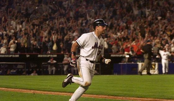 """In this Sept. 21, 2001, file photo, New York Mets' Mike Piazza rounds the bases on his two-run home run in the eighth inning against the Atlanta Braves at Shea Stadium in New York. A new exhibit at the National September 11 Memorial & Museum highlights the impact of sports after the 2001 attacks. """"Comeback Season: Sports After 9/11"""" explores how sports helped unite the country and features interviews with athletes, including Hall of Fame catcher Mike Piazza. (AP Photo/Jeff Zelevansky, File)  **FILE**"""
