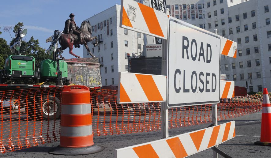Crews close roads as they prepare to remove the statue Confederate General J.E.B. Stuart on Monument Avenue Tuesday, July 7, 2020, in Richmond, Va. The statue is one of several that will be removed by the city as part of the Black Lives Matter reaction. (AP Photo/Steve Helber)