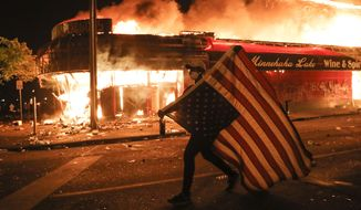 FILE - In this early Friday, May 29, 2020 file photo, a protester carries a U.S. flag upside, a sign of distress, next to a burning building in Minneapolis. Protests over the death of George Floyd, a black man who died in police custody Monday, broke out in Minneapolis and across the country. The U.S. has been dramatically disrupted in a matter of months, brought low by a global pandemic, Depression-era economic dislocation, and then, nationwide unrest over racial injustice. (AP Photo/Julio Cortez)
