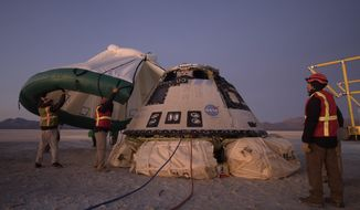 FILE - In this Sunday, Dec. 22, 2019 photo made available by NASA, Boeing, NASA, and U.S. Army personnel work around the Boeing Starliner spacecraft shortly after it landed in White Sands, N.M. On Tuesday, July 7, 2020, NASA officials said they have identified 80 corrective actions for safety, mostly involving software, that must be implemented before the Starliner capsule launches again. The previous count was 61.  (Bill Ingalls/NASA via AP)