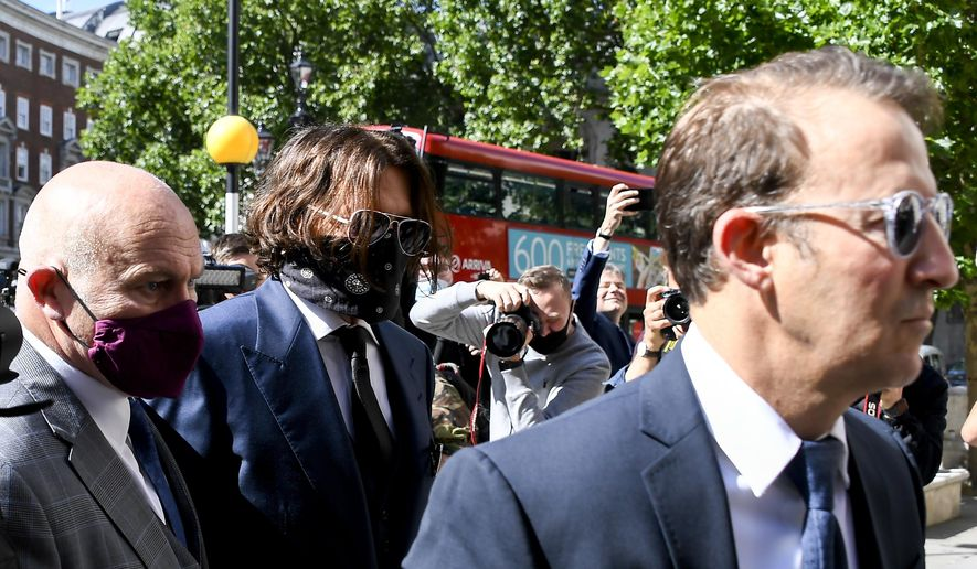"""Johnny Depp, second left, wearing a protective mask arrives at the Royal Court of Justice, in London, Tuesday, July 7, 2020. Johnny Depp is suing a tabloid newspaper for libel over an article that branded him a """"wife beater."""" On Tuesday, a judge at the High Court is due to begin hearing Depp's claim against The Sun's publisher, News Group Newspapers, and its executive editor, Dan Wootton, over the 2018 story alleging he was violent and abusive to then-wife Amber Heard. Depp strongly denies the claim. (AP Photo/Alberto Pezzali)"""