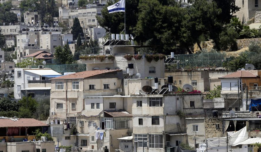 """An Israeli flag flies over a Jewish owned house in a Palestinian neighborhood of Silwan in east Jerusalem, Wednesday, July 1, 2020. Israeli leaders paint Jerusalem as a model of coexistence, the """"unified, eternal"""" capital of the Jewish people, where minorities have equal rights. But Palestinian residents face widespread discrimination, most lack citizenship and many live in fear of being forced out. (AP Photo/Mahmoud Illean)"""