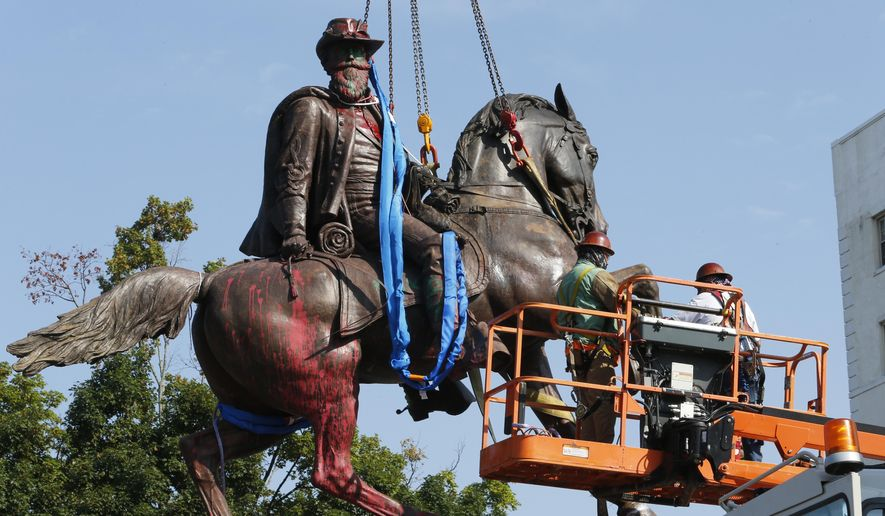 Crews attach straps to the statue Confederate General J.E.B. Stuart on Monument Avenue, Tuesday, July 7, 2020, in Richmond, Va. The statue is one of several that will be removed by the city as part of the Black Lives Matter reaction. (AP Photo/Steve Helber)