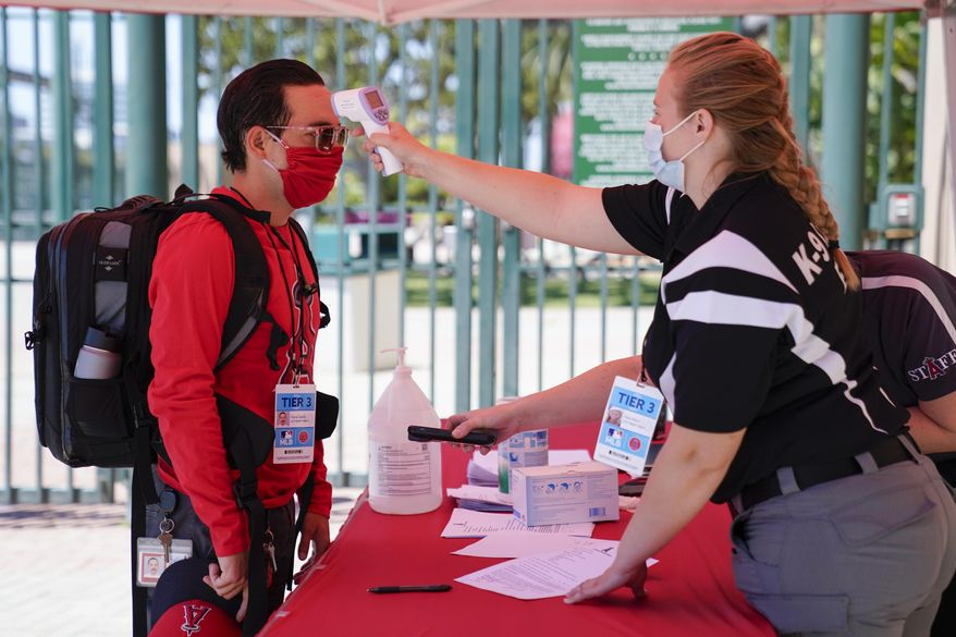 Ricardo Zapata, left, a photographer for the Los Angeles Angels, has his temperature taken by Sarah Morris before entering Angels Stadium for baseball practice on Monday, July 6, 2020, in Anaheim, Calif. New protocols like temperature checks, social distancing, and limiting amount of people allowed in sports venues have been put in place due to the spread of COVID-19. (AP Photo/Ashley Landis)