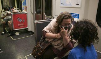 Lisa Fink holds a face covering to her mouth while talking to her son, Al, in a Metro Rail train Monday, July 6, 2020, in Los Angeles during the coronavirus pandemic. (AP Photo/Jae C. Hong)