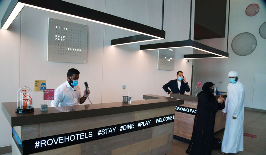 The front desk staff wearing masks due to the coronavirus pandemic help customers at the Rove City Centre Hotel in Dubai, United Arab Emirates, Monday, July 6, 2020. Dubai reopened for tourists Tuesday amid the coronavirus pandemic, hoping to reinvigorate a vital industry for this city-state before its crucial winter tourist season. (AP Photo/Jon Gambrell)