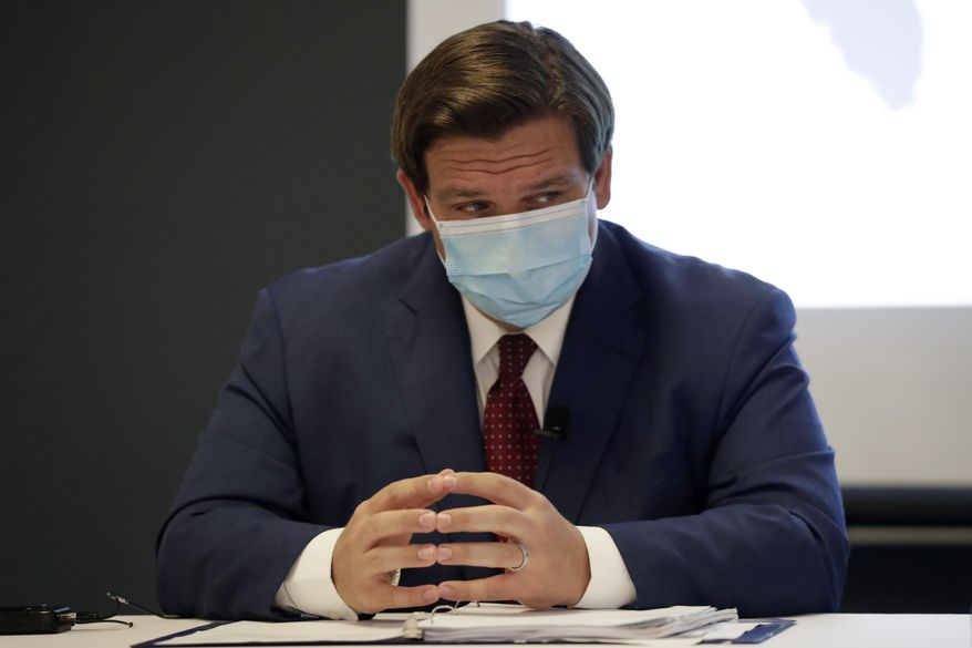 In this file photo, Florida Gov. Ron DeSantis listens during a news conference on Tuesday, July 7, 2020, in Miami. Florida Democrats are calling on Mr. DeSantis to institute lockdowns and a statewide mask mandate to combat rising COVID cases. (AP Photo/Lynne Sladky)  **FILE**