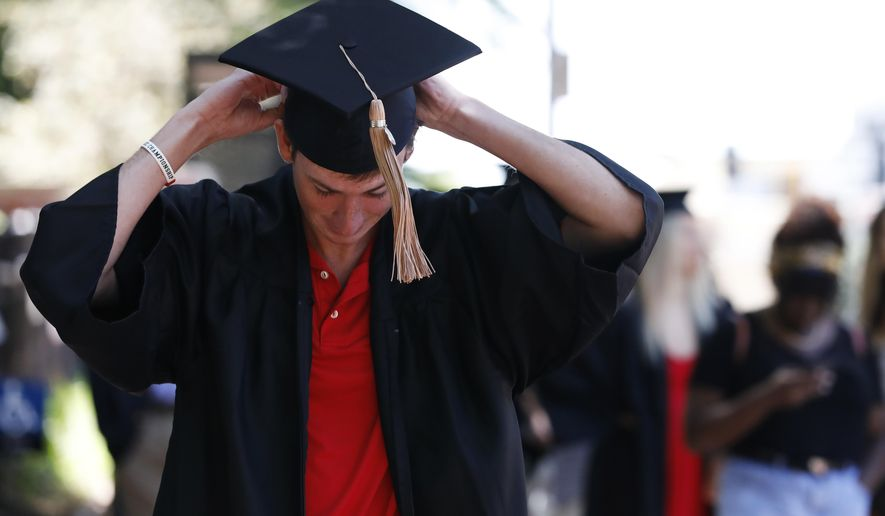 In this Thursday, May 7, 2020 photo, University of Georgia graduates line up to take photos at the University of Georgia arch  in Athens, Ga. The spring commencement, which would have been held on Friday, was moved to the fall due to the COVID-19 pandemic. (Joshua L. Jones/Athens Banner-Herald via AP)