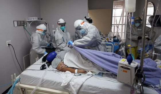 A blanket is pulled to cover the body of a patient after medical personnel tried without success to save her life inside the Coronavirus Unit at United Memorial Medical Center, Monday, July 6, 2020, in Houston. (AP Photo/David J. Phillip)