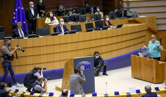 German Chancellor Angela Merkel, right, addresses the plenary chamber at the European Parliament in Brussels, Wednesday, July 8, 2020. Germany has just taken over the European Union's rotating presidency, and must chaperone the 27-nation bloc through a period of deep crisis for the next six months and try to limit the economic damage inflicted by the coronavirus. (AP Photo/Olivier Matthys)