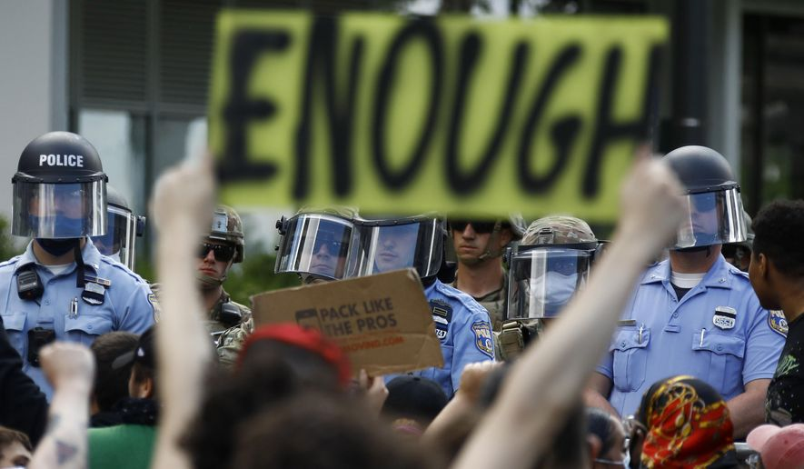 In this June 1, 2020, file photo, protesters rally as Philadelphia police officers and Pennsylvania National Guard soldiers look on in Philadelphia, over the death of George Floyd, a Black man who was in police custody in Minneapolis. (AP Photo/Matt Slocum, File)