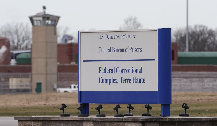 In this Dec. 10, 2019, file photo, the guard tower flanks the sign at the entrance to the U.S. Penitentiary in Terre Haute, Ind. (AP Photo/Michael Conroy, File)