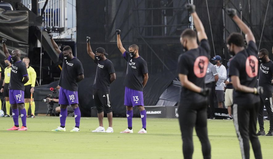 Orlando City players, left, raise their fists in the air in solidarity with other MLS teams before the start of an MLS soccer match, Wednesday, July 8, 2020, in Kissimmee, Fla., while wearing shirts and masks with messages about race. (AP Photo/John Raoux)