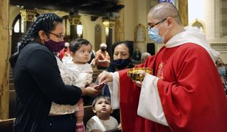 Parishioners receive the sacrament from the Rev. Luis Gabriel Medina during Communion at Saint Bartholomew Roman Catholic Church in the Queens borough of New York, Monday, July 7, 2020. This was the first in-person Mass at the church in almost four months. (AP Photo/Jessie Wardarski)