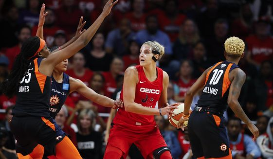 In this Oct. 10, 2019, file photo, Connecticut Sun forward Jonquel Jones, left, and guard Courtney Williams, right, guard Washington Mystics forward Elena Delle Donne during the first half of Game 5 of basketball's WNBA Finals in Washington. Delle Donne is waiting to have her case heard by the league's independent panel of doctors to see if she'll be medically excused for the season, according to the Mystics.The Mystics star, who was the league Most Valuable Player last year, has battled Lyme Disease since 2008 and would potentially be at a higher risk for serious illness if she contracted the new coronavirus. (AP Photo/Alex Brandon) ** FILE **