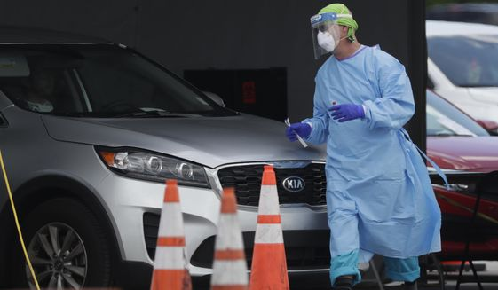 A healthcare worker walks around a car to test a passenger at a drive-through COVID-19 testing site outside Hard Rock Stadium, Wednesday, July 8, 2020, in Miami Gardens, Fla. Florida is one of the nation's hot spots for coronavirus. Almost 10,000 confirmed cases were added Wednesday, bringing its total since March 1 to nearly 224,000. Almost 4,000 people have died, including 48 reported by the state Wednesday. (AP Photo/Wilfredo Lee)