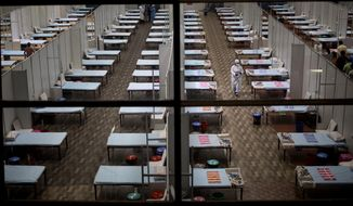 A hospital staff walks past rows of beds at a makeshift COVID-19 care center at an indoor sports stadium in New Delhi, India, Wednesday, July 8, 2020. India has overtaken Russia to become the third worst-affected nation by the coronavirus pandemic. (AP Photo/Altaf Qadri)
