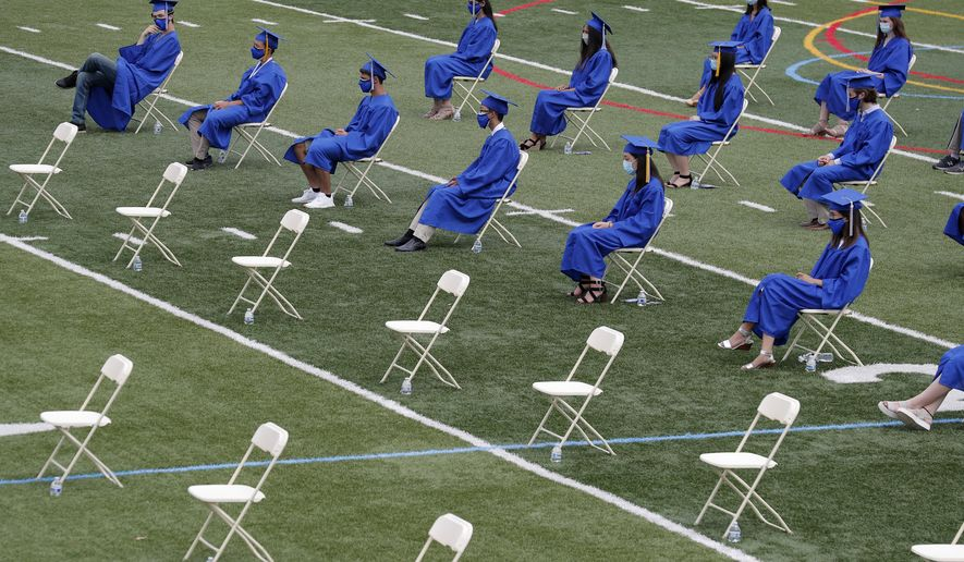 In this file photo, graduating students socially distance by sitting far apart during a graduation ceremony at Millburn High School in Millburn, N.J., Wednesday, July 8, 2020. T (AP Photo/Seth Wenig)  **FILE**
