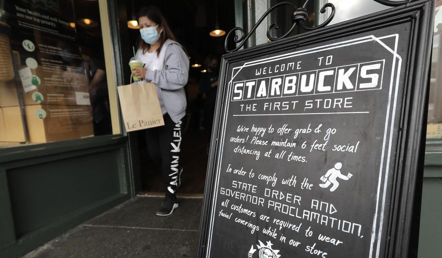 A customer walks out of the first Starbucks store, Tuesday, July 7, 2020, at Pike Place Market in Seattle. Tuesday was the first day of a new statewide order that requires people to wear masks or other facial coverings inside businesses in hopes of slowing the spread of the coronavirus. Business owners who fail to refuse service to customers who don't wear masks can face fines or lose their business license, but some business owners have raised concerns about turning away customers. (AP Photo/Ted S. Warren)