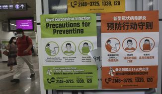People wearing face masks pass by posters about precautions against new coronavirus at a subway station in Seoul, South Korea, Wednesday, July 8, 2020. (AP Photo/Ahn Young-joon)