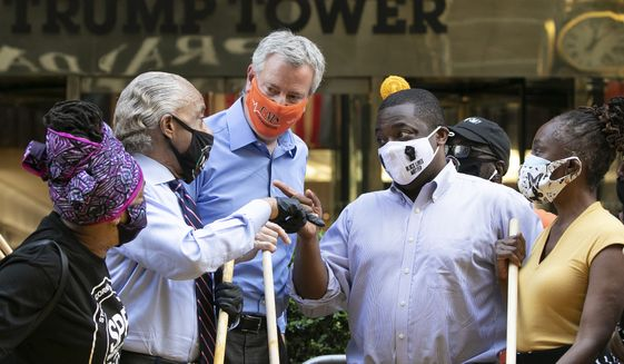 Mayor Bill de Blasio, center with orange mask, talks with Rev. Al Sharpton, second from left, while painting Black Lives Matter on Fifth Avenue in front of Trump Tower, Thursday, July 9, 2020, in New York. The mayor's wife, Chirlane McCray, is on the right. The others are unidentified. (AP Photo/Mark Lennihan)