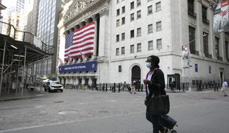 A woman wearing a mask walks by the New York Stock Exchange during the coronavirus pandemic, Thursday, July 9, 2020, in New York. (AP Photo/Mark Lennihan)