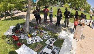 FILE - In this Monday, June 15, 2020, file photo, people stand by a memorial as they gather near the site where Robert Fuller was found hanged in Palmdale, Calif. A police investigation confirmed suicide was the cause of death of Fuller, a Black man found hanging from a tree in a Southern California city park last month, authorities said Thursday, July 9, 2020. (AP Photo/Mark J. Terrill, File)