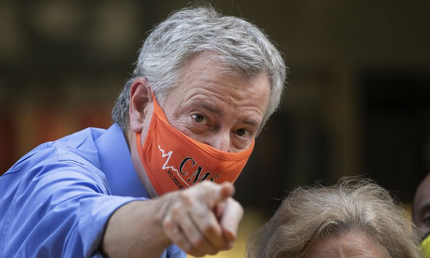Mayor Bill de Blasio points to the crowd while painting Black Lives Matter on Fifth Avenue in front of Trump Tower, Thursday, July 9, 2020, in New York. (AP Photo/Mark Lennihan)