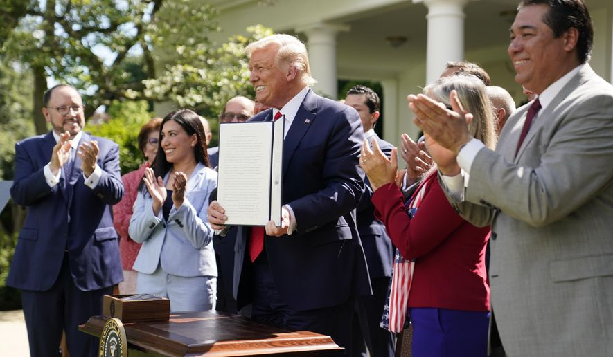 "President Donald Trump holds an executive order on the ""White House Hispanic Prosperity Initiative,"" after signing it in the Rose Garden of the White House, Thursday, July 9, 2020, in Washington. (AP Photo/Evan Vucci)"