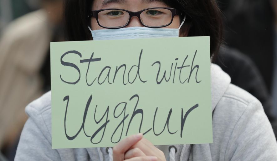 In this Dec. 22, 2019, file photo, a man holds a sign during a rally to show support for Uighurs and their fight for human rights in Hong Kong. People from western China who are targets of a Chinese government crackdown say they have been threatened and harassed in the United States. Those fleeing the crackdown on the predominantly Muslim Uighur ethnic group typically receive U.S. asylum. But Uighurs tell The Associated Press and human rights groups they still afraid amid threats aimed at them and their families back in China. (AP Photo/Lee Jin-man, File)