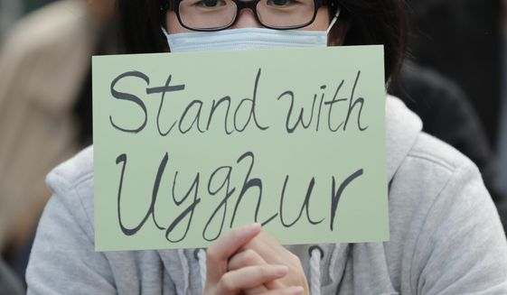 FILE - In this Dec. 22, 2019, file photo, a man holds a sign during a rally to show support for Uighurs and their fight for human rights in Hong Kong. People from western China who are targets of a Chinese government crackdown say they have been threatened and harassed in the United States. Those fleeing the crackdown on the predominantly Muslim Uighur ethnic group typically receive U.S. asylum. But Uighurs tell The Associated Press and human rights groups they still afraid amid threats aimed at them and their families back in China. (AP Photo/Lee Jin-man, File)