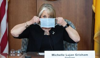 In this April 15, 2020, file photo, New Mexico Gov. Michelle Lujan Grisham puts on her face mask when not speaking during an update on the COVID-19 outbreak in the state during a news conference in the state Capitol in Santa Fe, N.M. Gov. Lujan Grisham used her line-item veto power to preserve executive control over hundreds of millions of dollars in federal coronavirus relief funding, a move that could mean the loss of additional financial assistance for some Native American communities. She used her veto pen to scratch out entire paragraphs of the budget to prevent the Legislature from earmarking $318 million in federal virus relief funding for local governments. (Eddie Moore/The Albuquerque Journal via AP, Pool, File)
