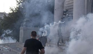 A man hurls a tear gas canister at riot police on the steps of the Serbian parliament during a protest in Belgrade, Serbia, Wednesday, July 8, 2020. Police have fired tear gas at protesters in Serbia's capital during the second day of demonstrations against the president's handling of the country's coronavirus outbreak. President Aleksandar Vucic backtracked on his plans to reinstate a coronavirus lockdown in Belgrade this week, but it didn't stop people from firing flares and throwing stones while trying to storm the downtown parliament building. (AP Photo/Marko Drobnjakovic)